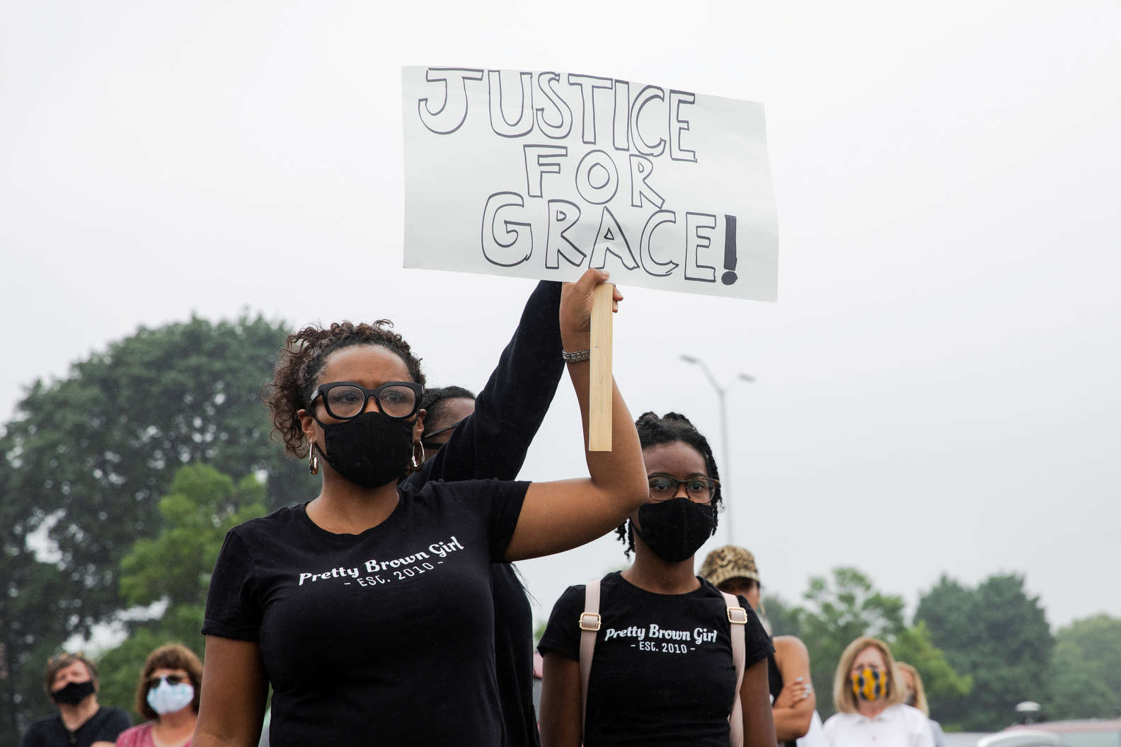 "Woman holding ""Justice For Grace"" sign"