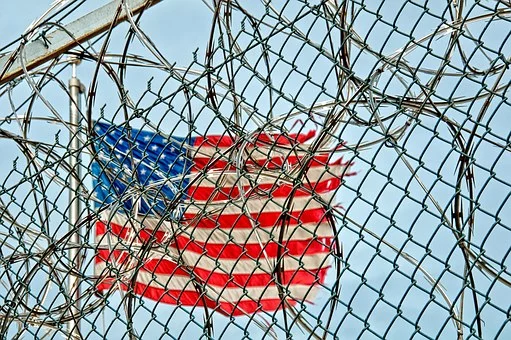 US Flag waving behind barbed wire