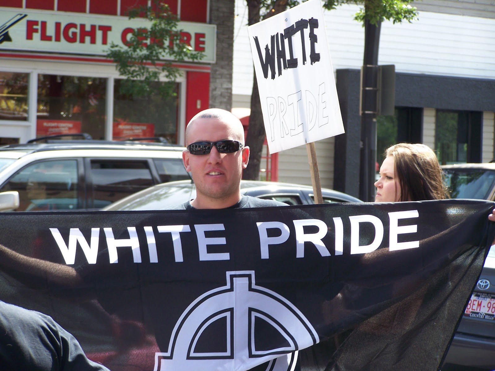 Man holding white pride sign