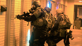 Militarized Police with guns drawn in front of doors