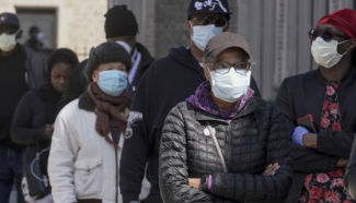 People in a line with face masks