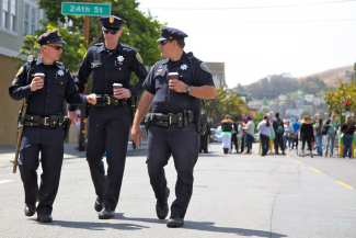 Cops walking with coffee away from a crowd