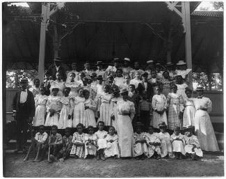 Black children in pavilion with a few adults circa 1899