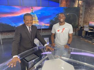 Student smiling with anchor at news desk