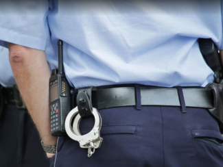 Police handcuffs, radio and gun in officer's belt holster