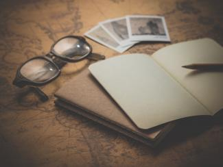A pair of glasses, photos and journal on a world map